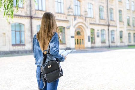 Denim jeans casual clothes start teacher job people career summer concept. Back behind rear close up view photo portrait of confident stressed girl holding book diary in hands blurred background Stock Photo