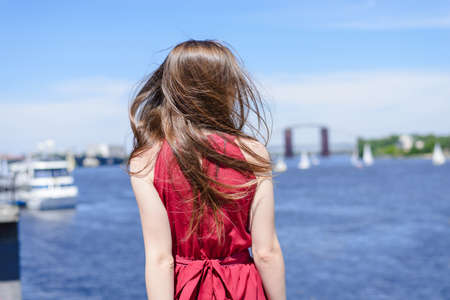 Blue water beauty nature sly clouds resort tour deck cruise concept. Rear back behind view portrait photo of beautiful pretty lady looking at the lake near city wearing elegant burgundy shiny outfit Stok Fotoğraf