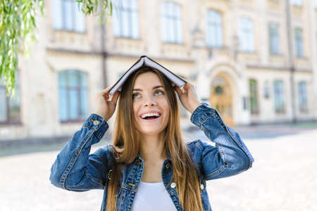 Close up photo portrait of cute pretty crazy attractive with long hair person holding book on head Banco de Imagens