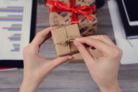 Pov high angle first person overhead view close up photo of beautiful red ribbon bow paper wrapped closed package unwrapped unpack in hands over wooden table