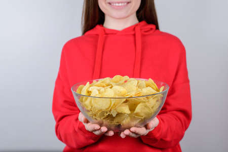 Cropped closeup photo portrait of positive cheerful cool hungry in red bright pullover girl teen holding large big bowl in hands isolated grey background