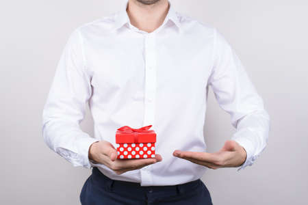 Close up photo of handsome happy masculine charming in formalwear clear classic classy chic shirt man holding little paper dotted box in hand isolated grey background