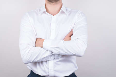 Cropped closeup photo portrait of serious single macho gentleman holding arms hands crossed wearing clear clean with collar shirt isolated grey background