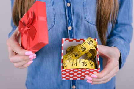 Cropped closeup photo of unhappy shocked amazed sad upset she her lady holding box with tape measure inside she package isolated grey background