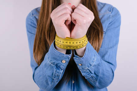 Cropped closeup photo portrait of unhappy tired exhausted sad hungry she lady showing tied hands arms with yellow centimeter isolated grey background