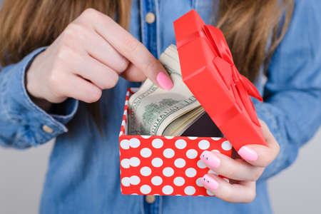Cropped closeup photo of hands holding red small box full of money isolated grey background