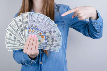 Closeup photo portrait of confident satisfied she her businesspeople holding pile of money in hand demonstrating indexing with forefinger isolated grey background