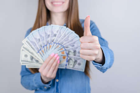 Cropped close-up photo portrait of beautiful pretty positive she her lady holding money in hand giving making finger up approve offer advert advice symbol isolated grey background