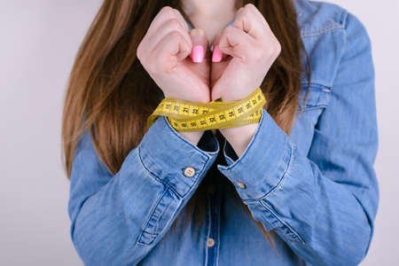 Sugar avoid sweet calories choose decision people person concept. Cropped closeup photo of determined will-powered slim thin slender lady showing tied hands yellow centimeter isolated grey background