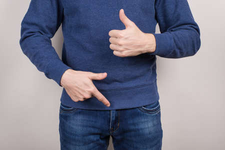 Cropped close-up photo of satisfied confident cool guy demonstrating pointing on his he organ in pants trousers isolated grey background Stok Fotoğraf