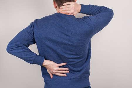 Zurück hinter hinten Nahaufnahme abgeschnittenes Foto eines unglücklichen traurigen verärgerten Geschäftsmannes, der Hals und Rücken isoliert grauer Hintergrund hält
