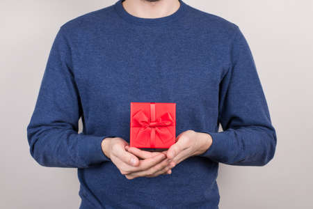 Cropped close-up photo studio shot of cheerful good glad positive optimistic person showing beautiful nice square container for expensive present in palms isolated grey background Stok Fotoğraf