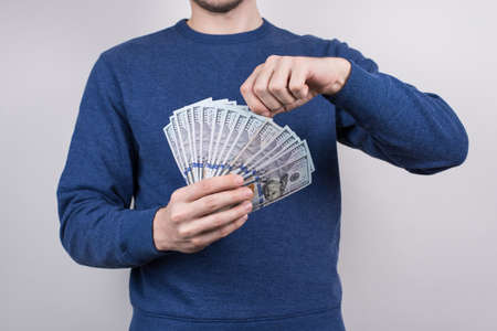Cropped closeup studio photo of confident human showing lot of money in palms wearing sweater pullover jumper isolated grey background Stok Fotoğraf
