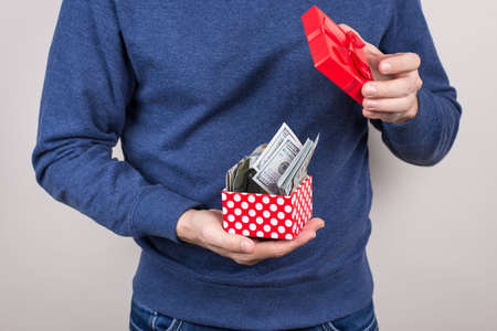 Cropped close-up photo shot of student holding small red little package full of money isolated grye background