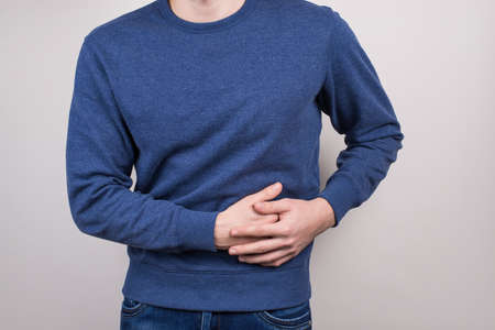 Unhealthy eating nutrition concept. Cropped closeup photo of unhappy sad guy touching left side feeling severe pain isolated grey background