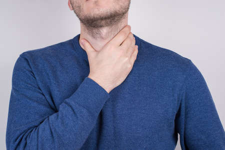 Cropped closeup photo shot of unhappy sad upset guy touching neck with hand isolated grey background Stock Photo