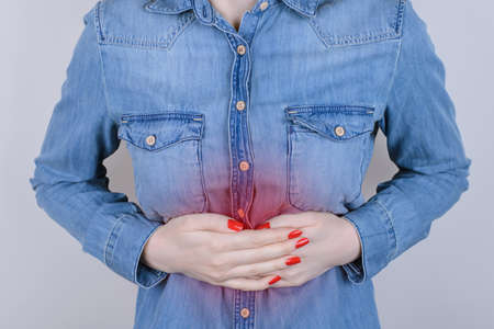 Digestion indigestion people person concept. Cropped close up photo of sad unhappy stressed depressed lady suffering from stomach-ache isolated on gray background Imagens