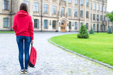 Back rear behind full length bosy size photo of serious confident concentrated hipster holding schoolbag in hand looking at the entrance standing near green lawn Stockfoto