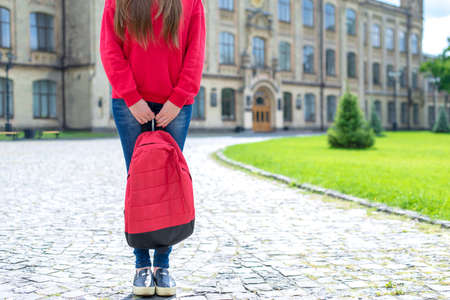 Cropped photo of teen standing near university ready for new year holding satchel in hands wearing denim outfit