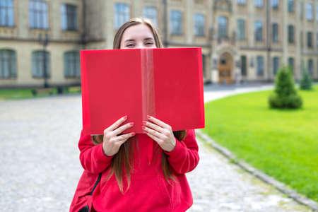 Fotoporträt des charmanten, schönen, fröhlichen, aufgeregten Teen Hipster Millennial Closing, der ihr Gesicht bedeckt und mit einem großen offenen Buch lächelt