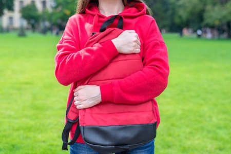 Cropped close-up photo of person hugging with two hands her satchel near highschool. Green grass is on the background