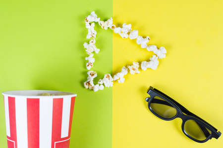 I like love adore watching new film concept. Top above high angle overhead close up view bright photo of play button with tasty popcorn and black 3d glasses isolated over two parts halves background Banco de Imagens