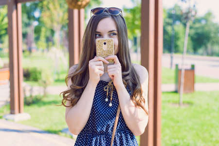 Photo of laughing funny funky pondering thinking over her plan pensive interested model holding telephone in hands closing face looking away to the side park on the background