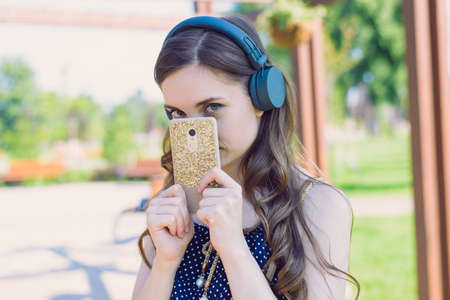 Closeup photo portrait of pretty attractive sweet lovely with coquettish looking at you eyes hiding face behind golden telephone case Imagens
