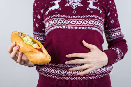 I am full concept. Cropped close up photo of girl feeling bad after eating lot of meal and junk food holding touching painful stomach with palm isolated grey background