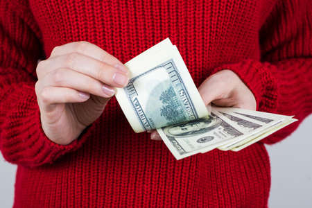 Cropped close up photo of hands of worker counting paper money going to spend all her wage in one day wearing bright knitted pullover isolated grey background