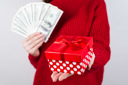 Winning money concept. Cropped closeup photo of happy joyful girl cheerful woman holding small giftbox in hands isolated grey background Stock Photo