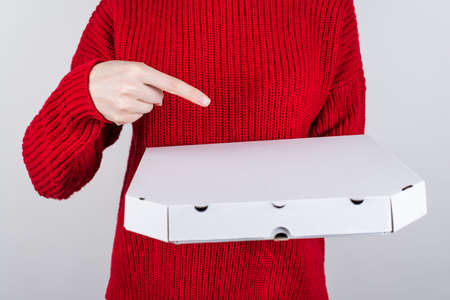 Cropped close up photo of woman in bright jumper demonstrating white paper container with delicious pizza inside isolated grey background copy space