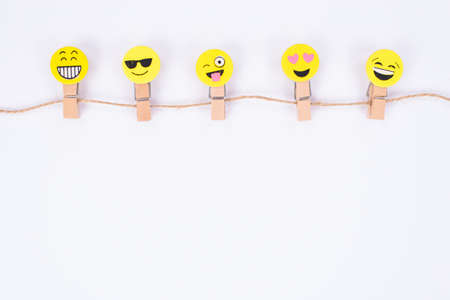 Top above high angle close up view photo of five nice glad smiley faces hanging on string isolated white wall Stock fotó