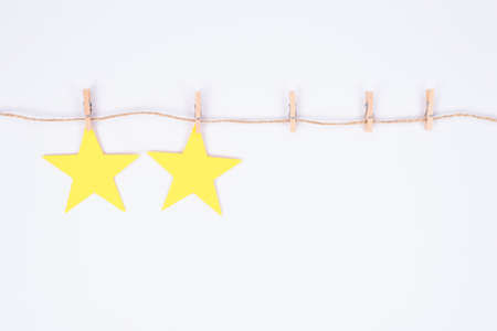 Photo of two rating stars hanging on thread attached with little clothespins isolated white background