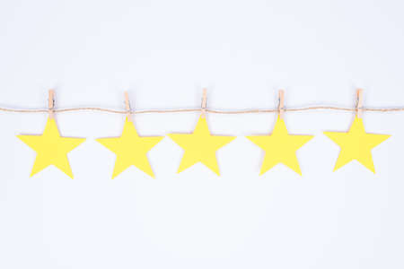 Positive feedback concept. Close up photo of five small golden stars hanging on thread attached with small clothespins isolated white background