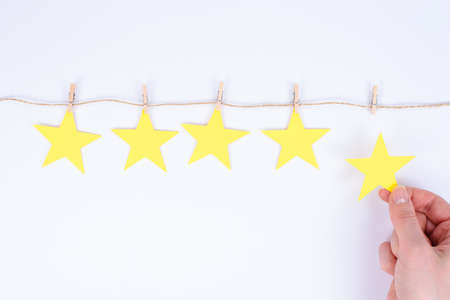 Young woman is giving her feedback by placing fifth star to the rating holding small star isolated white background Banco de Imagens