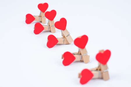 Group sex concept. Close up photo of clothespins with red hearts isolated on white background Standard-Bild - 139988673