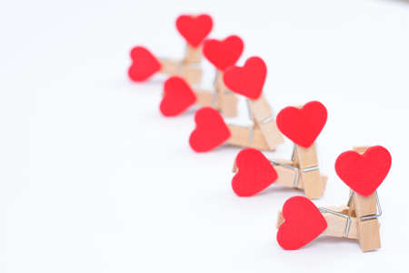 Group sex concept. Close up photo of clothespins with red hearts isolated on white background Standard-Bild - 139988677