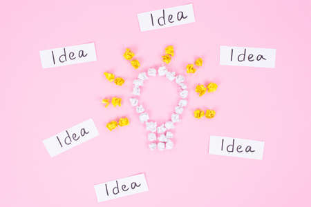 Finding lot of many great ideas. High angle view of shining light bulb made of white crumpled yellow and white paper with text words idea around isolated