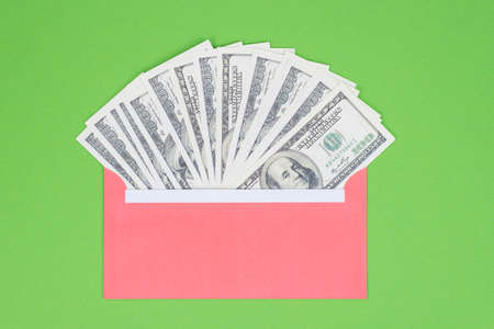 Getting credit deposit money from bank concept. Top above close up view photo of red envelope full of money isolated over bright green background