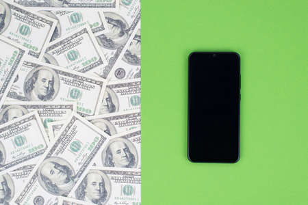 Top above flat lay close up view photo of smart phone with touch screen isolated on halved bright green and money print pattern template background