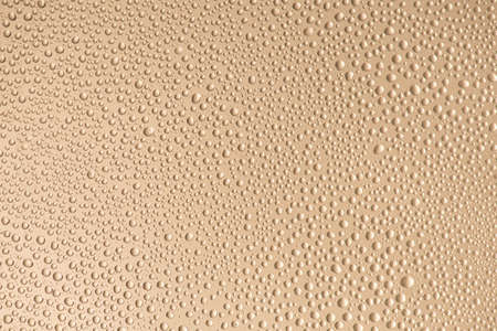 Close up photo of little water drops with contour shadow isolated on beige color background