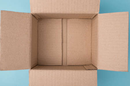 Top overhead above closeup view photo of unpacked empty box on blue background with blank copy space
