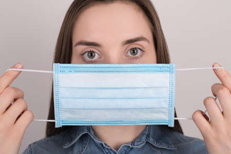 Coronavirus protection concept. Close up photo of young woman wearing blue medical mask on face isolated on grey background