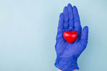 Heart care concept. Top above close up overhead view photo of hand showing small red heart in hand isolated over blue color background with copy empty blank space