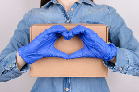 Delivery with support care about every client concept. Cropped close up girl in jeans shirt hugging embracing holding craft paper box and making showing heart isolated over gray background Stock Photo