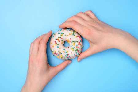 Top above flat lay flatlay overhead close up view photo of hands taking buying tasty fresh sugary donut ready to eat isolated over pastel color table background