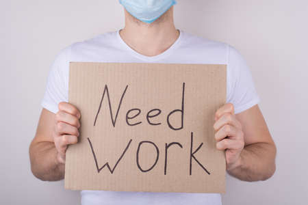 Looking for a job after qauarantine concept. Cropped close up photo of man wearing surgical safety mask and showing in hands cardboard placard with text isolated grey background