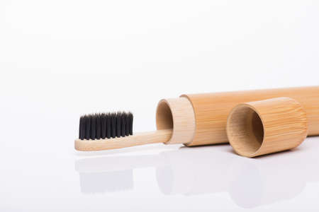 Close-up side profile macro view photo of eco-friendly bamboo packed in travel case black toothbrush isolated on white background