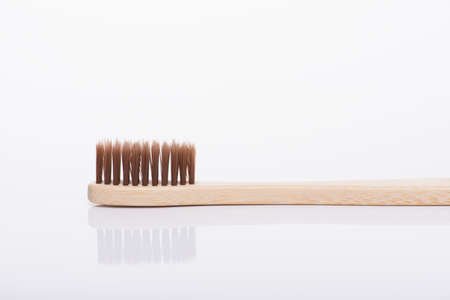 Zero waste concept. Close-up side profile macro view photo of eco-friendly brown toothbrush isolated on white background Banque d'images